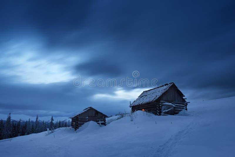 Casas de madera en las montañas en invierno foto de archivo