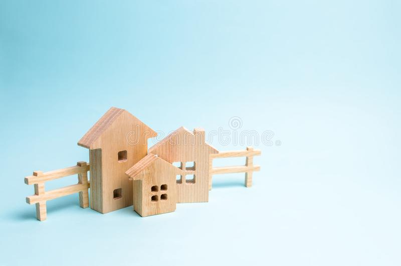 Casas de madera en un fondo azul Juguetes de madera El concepto de propiedades y propiedad inmobiliaria, la compra y venta de la  foto de archivo libre de regalías