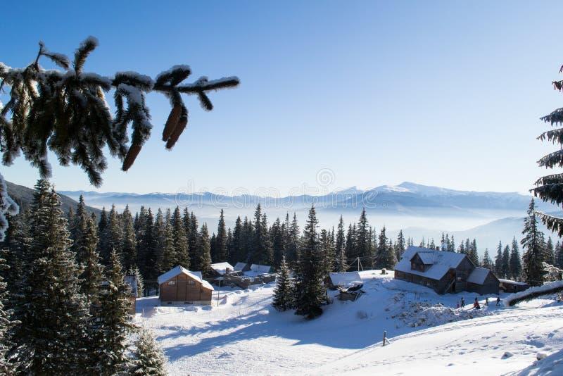 Casas de madera entre las montañas y los abetos imagen de archivo