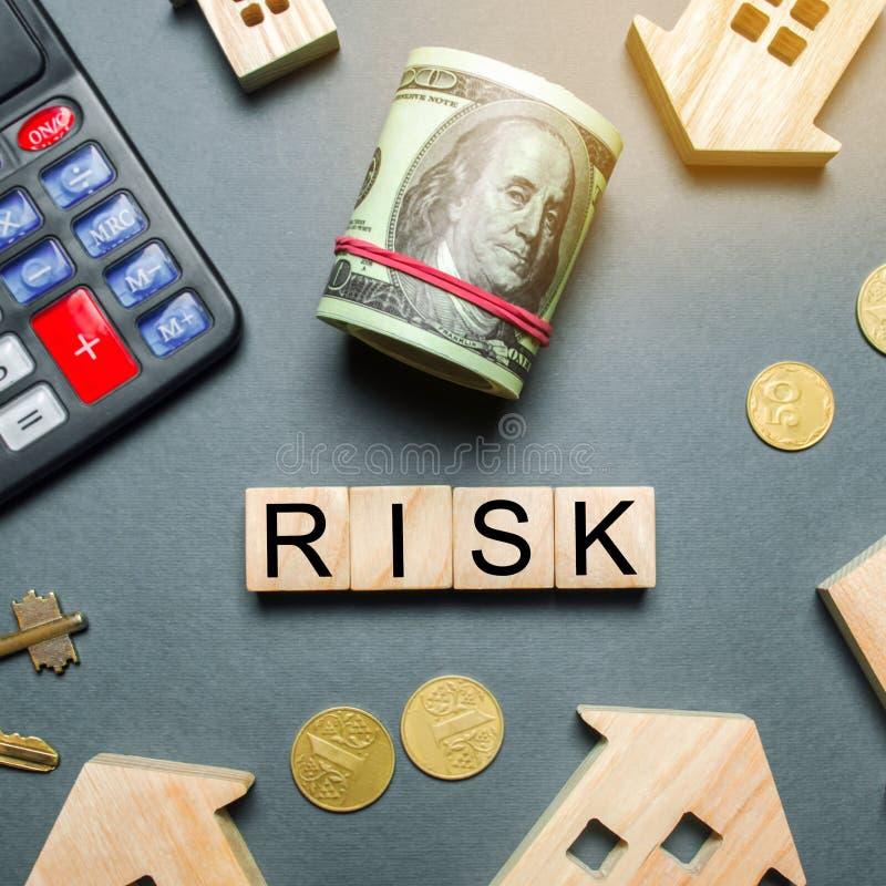 Casas de madera, una calculadora, llaves, monedas y bloques con el riesgo de la palabra Los riesgos de inversi?n en propiedades i fotografía de archivo