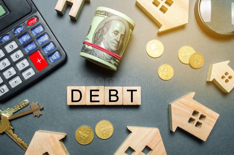 Casas de madera, una calculadora, llaves, monedas y bloques con la deuda de la palabra El concepto de deuda para contener Hipotec imagenes de archivo