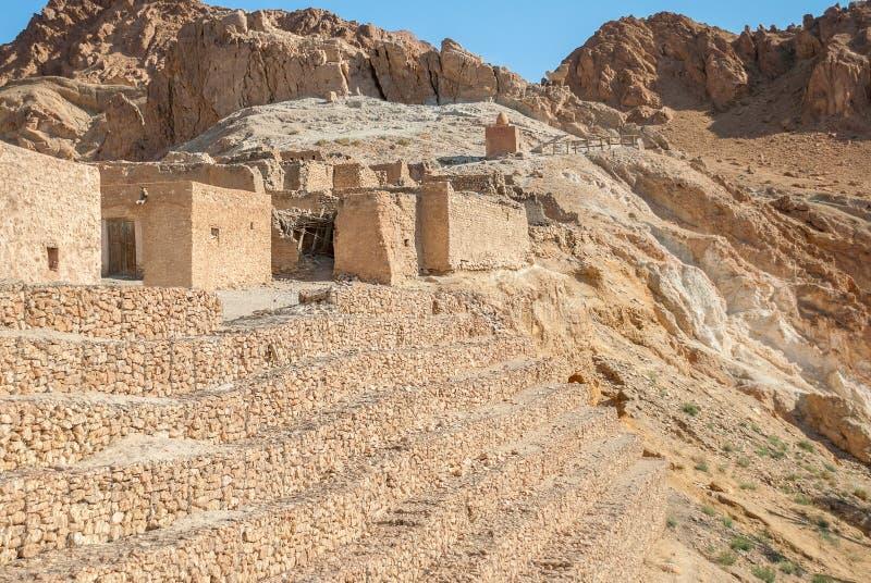 Casas de pedra arruinadas no deserto contra o contexto das montanhas altas fotos de stock