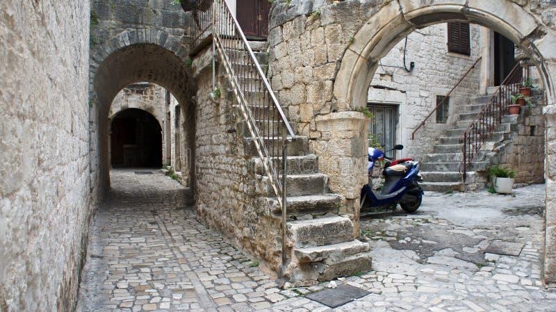 Casas de piedra en calle estrecha de la ciudad vieja, arquitectura hermosa con los archs y escaleras, día soleado, Trogir, Dalmac imagen de archivo