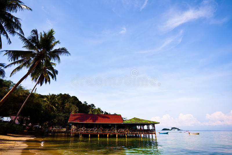 Casas de planta baja en el agua y las palmas imagen de archivo libre de regalías