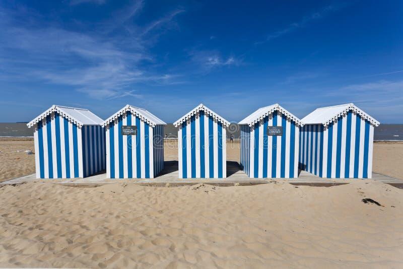 Casas de playa rayadas blancas y azules en una playa asoleada imágenes de archivo libres de regalías