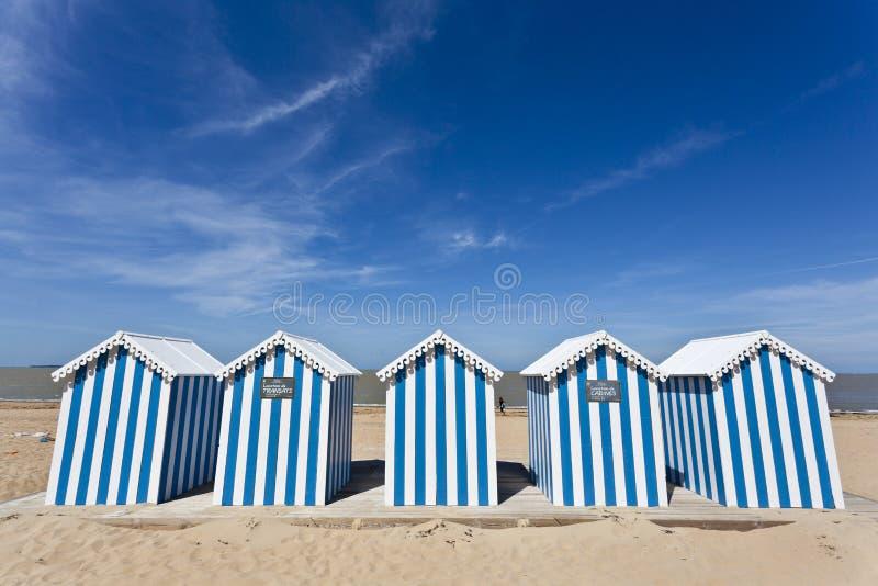 Casas de playa rayadas blancas y azules en una playa asoleada fotografía de archivo