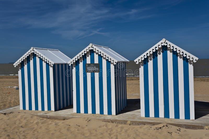 Casas de playa rayadas blancas y azules en una playa asoleada imagen de archivo libre de regalías