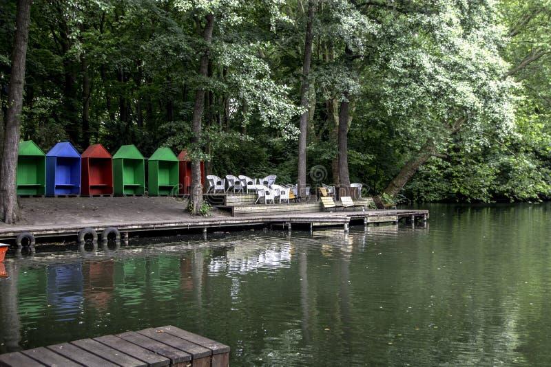 Casas de praia vermelhas, azuis e verdes perto de um lago imagens de stock royalty free