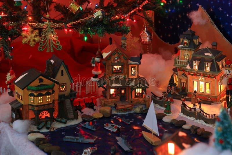 Casas del pueblo de la Navidad debajo de un árbol imagen de archivo libre de regalías