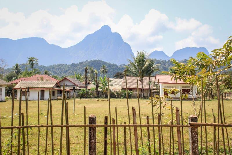 Casas del pueblo detrás de la cerca en el pueblo de Vang Vieng, Laos contra el contexto de montañas fotos de archivo libres de regalías