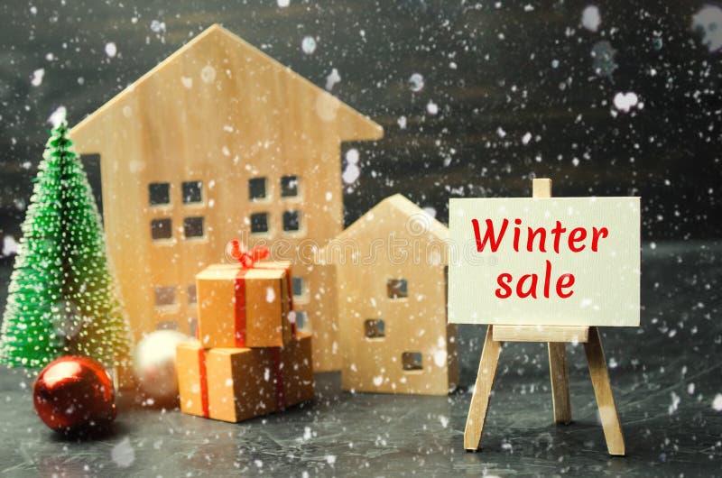 Casas e árvore de Natal de madeira com a venda do inverno da inscrição Venda do Natal de Real Estate Descontos do ano novo para c imagem de stock royalty free