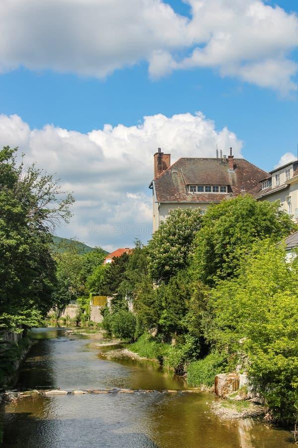 Casas e árvores nos bancos do córrego de Muhlbach em Baden Áustria imagem de stock