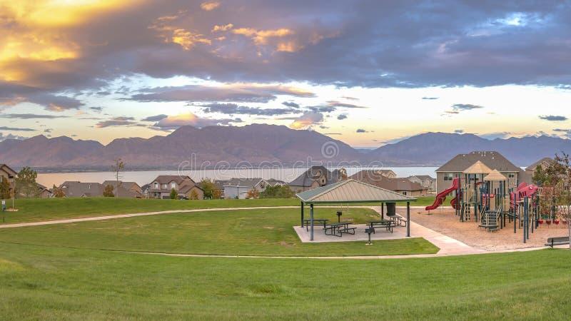 Casas e campo de jogos com lago e Mountain View fotos de stock royalty free