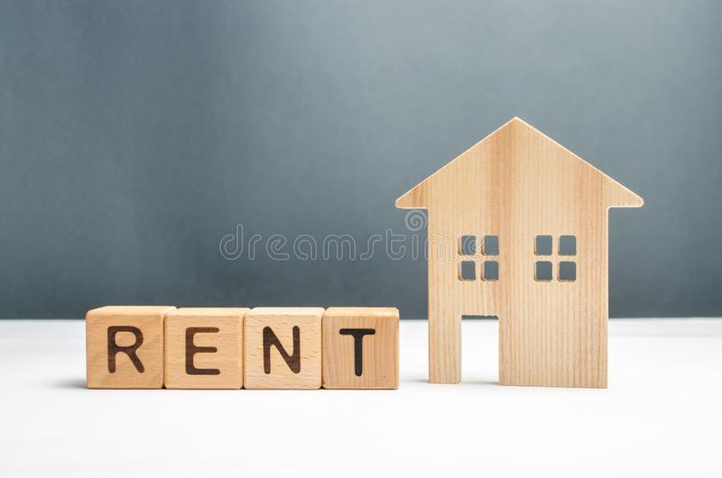 Casas e cubos de madeira da estatueta com o aluguel da palavra Busca para abrigar para o arrendamento do aluguel ou da propriedad fotografia de stock royalty free