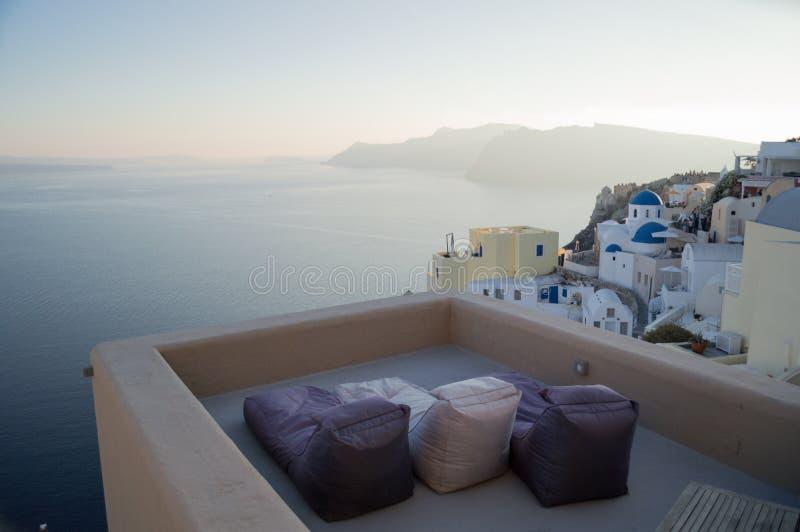 Casas e iglesia blanqueadas en los acantilados con la opinión y Sunbed del mar fotografía de archivo