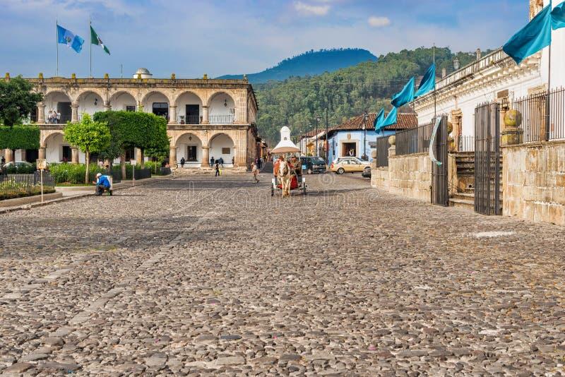 Casas e tráfego pela plaza principal em Antígua, Guatemala imagem de stock royalty free