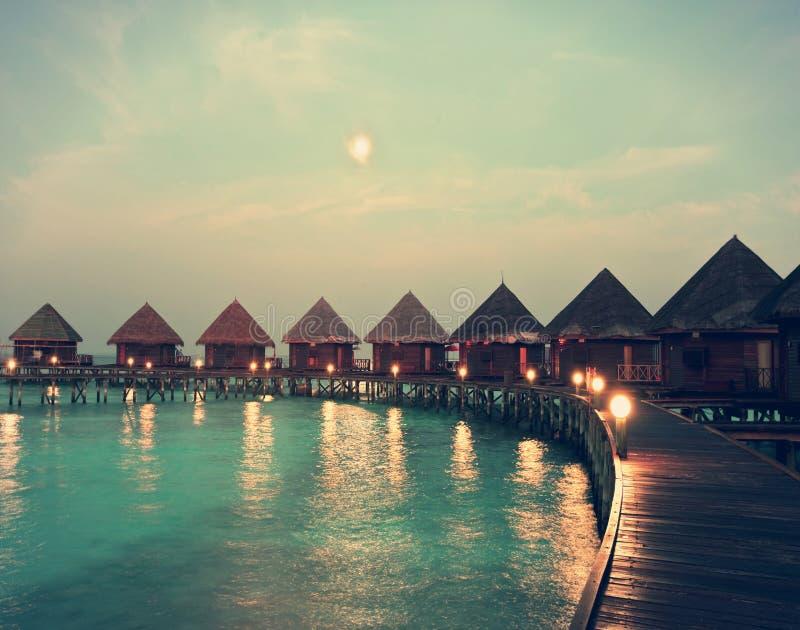 Casas em pilhas na água na noite na luz de lua do tolo, com um efeito retro imagem de stock