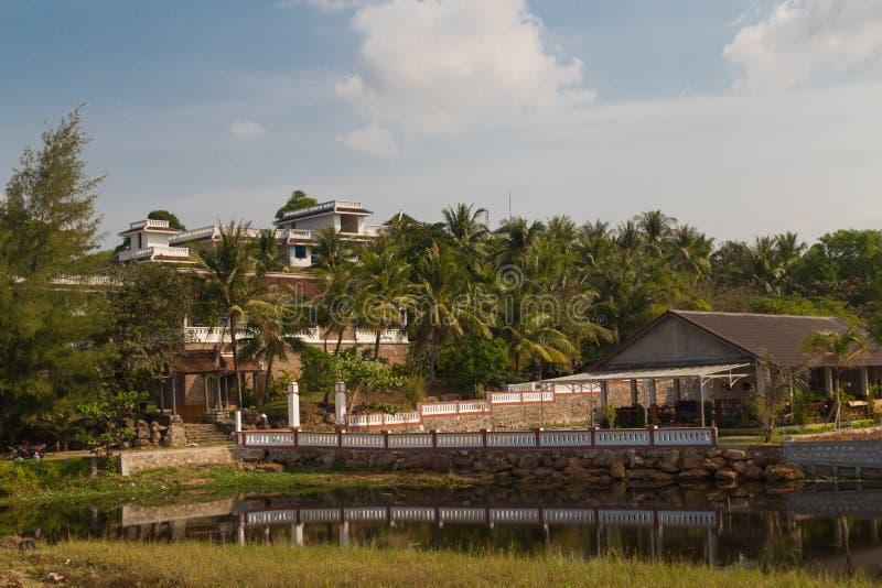 Casas en la orilla de un lago tropical imagen de archivo libre de regalías