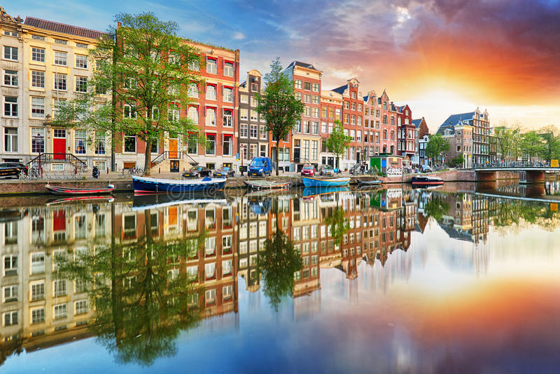 Casas en las reflexiones de la puesta del sol, Países Bajos, panor del canal de Amsterdam imagen de archivo
