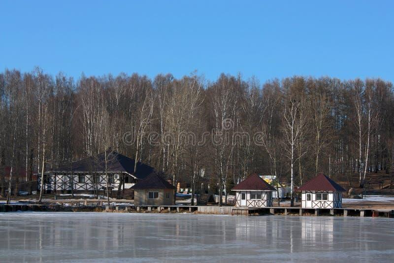 Casas entre abedules en el lago helado imagen de archivo libre de regalías