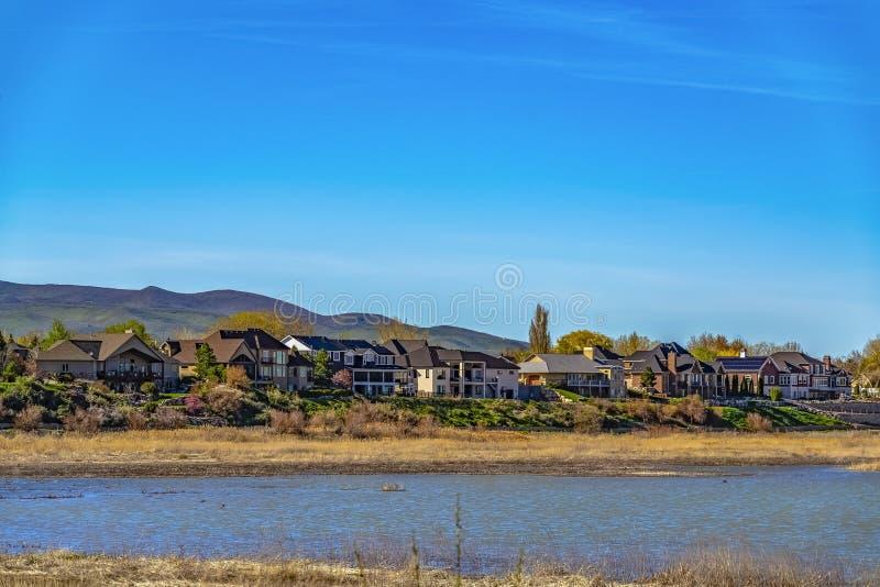 Casas entre a folha luxúria que negligencia um lago com gramas marrons na costa imagem de stock royalty free