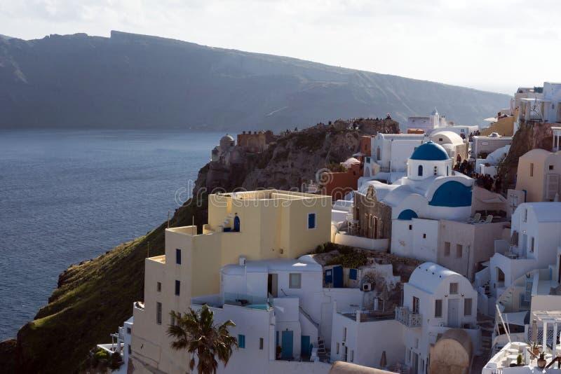 Casas griegas tradicionales blancas en una ladera en la isla de Santorini fotografía de archivo