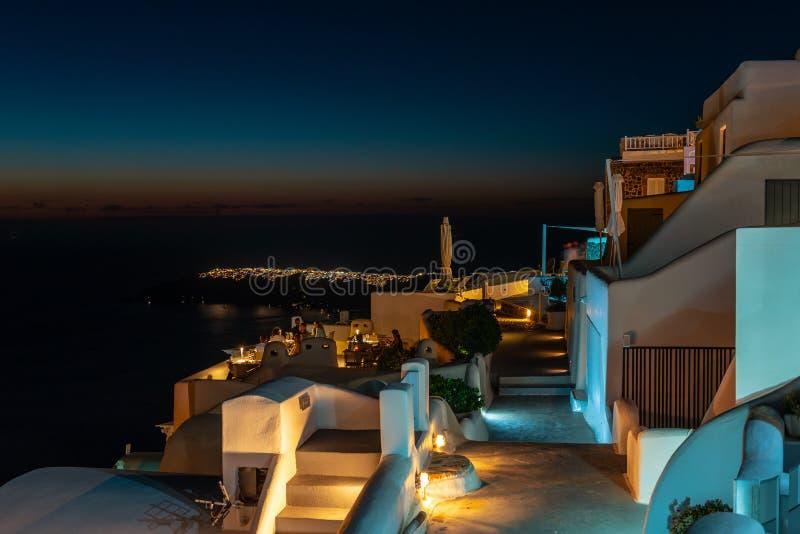 Casas griegas tradicionales iluminadas con las luces hermosas durante noche de verano imagenes de archivo