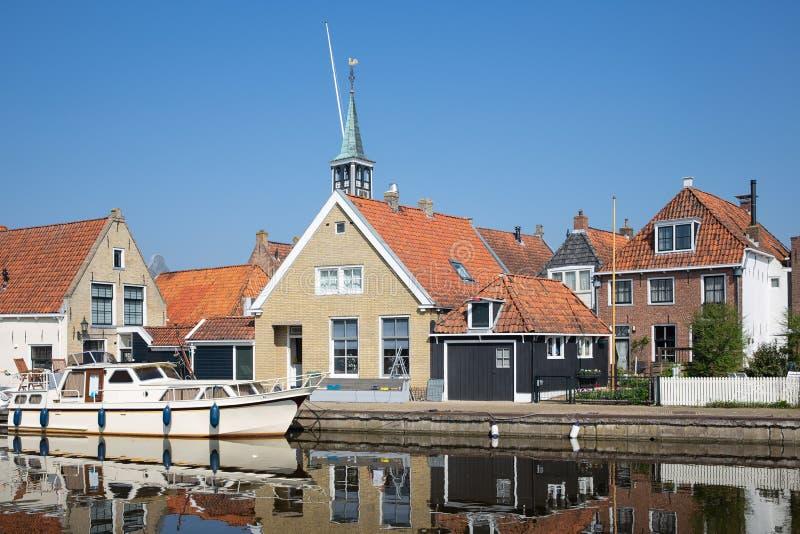 Casas a lo largo de un canal en Makkum, un pueblo holandés viejo imagen de archivo