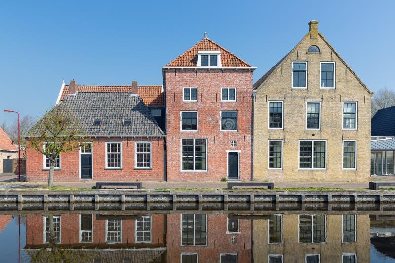 Casas a lo largo de un canal en Makkum, un pueblo holandés viejo foto de archivo libre de regalías
