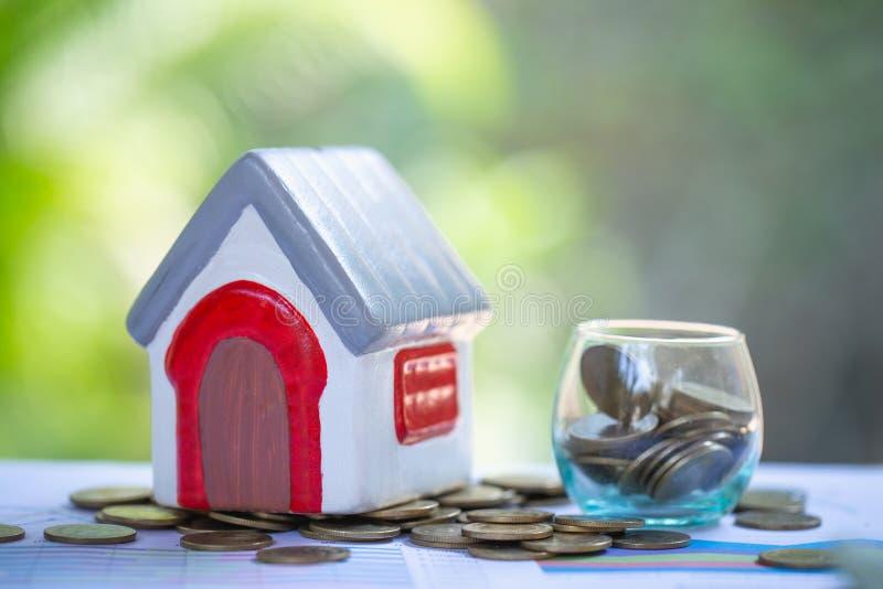 Casas miniatura entre la pila de plan y de estrategia de ahorro residencial de impuesto, hipoteca, inversión de las monedas, de l imagen de archivo
