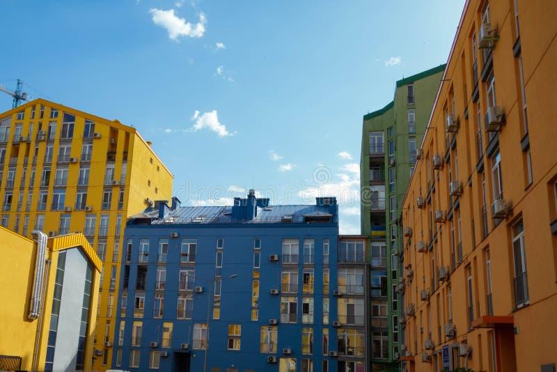 Casas modernas bonitas pintadas em cores brilhantes C?u azul e nuvens bonitos sistema e arco-?ris Auto-molhando nos jatos da ?gua fotografia de stock royalty free