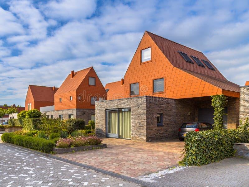 Casas modernas de la arquitectura con las tejas de tejado rojas imagen de archivo