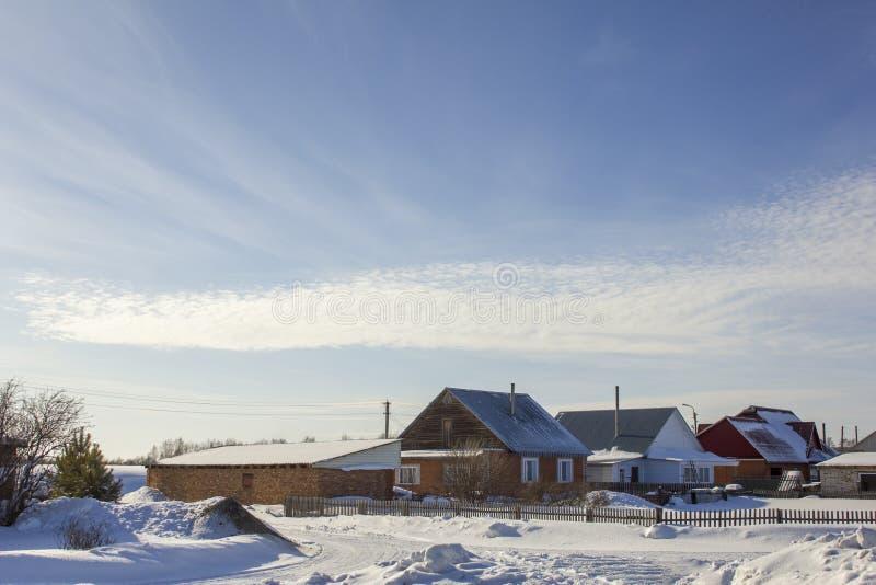 Casas modernas del pueblo debajo de un cielo azul con las nubes blancas en paisaje del invierno imagen de archivo