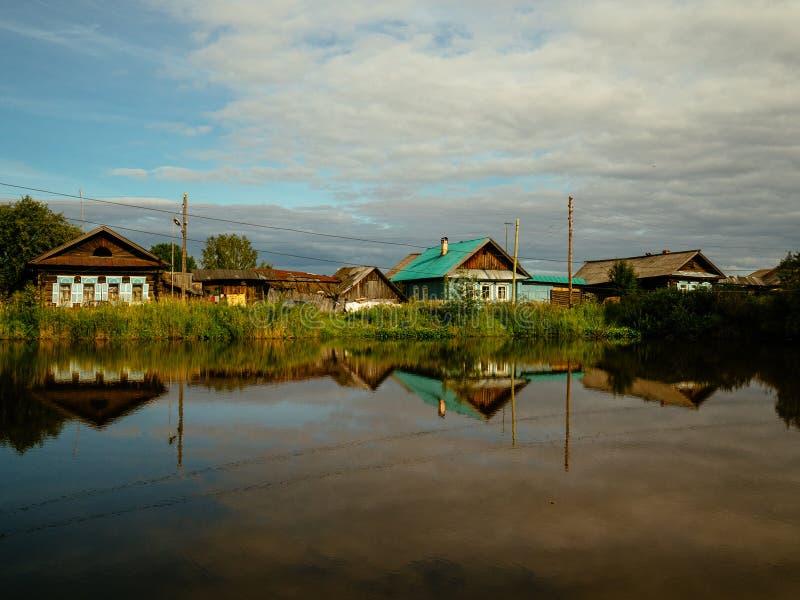 Casas na vila ao lado do lago são refletidas da superfície da água fotografia de stock
