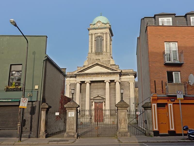 Casas ocultadas iglesia del behindd en una calle en Dublín foto de archivo