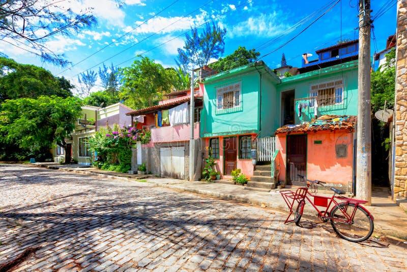 Casas pequenas coloridas ao longo de uma rua cobbled em Buzios, Brasil imagem de stock royalty free
