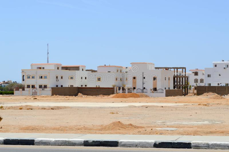 Casas rectangulares árabes en el desierto con las ventanas contra la perspectiva de la arena amarilla y cielo azul en Egipto y ne imagen de archivo