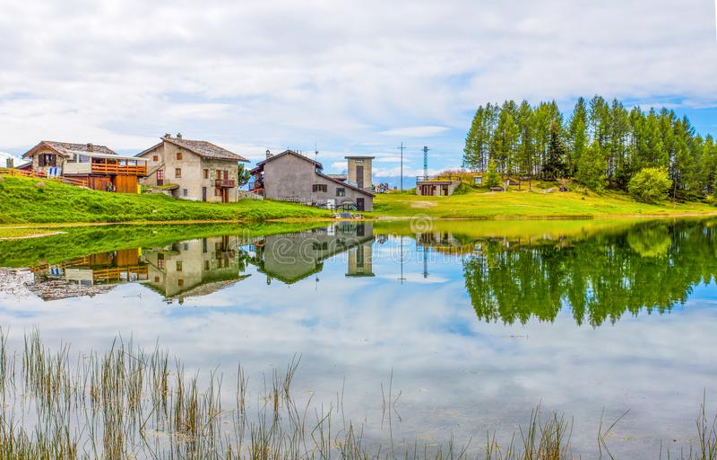 Casas reflejadas en el lago Lod cerca del pueblo de la gamuza en el ` Aosta, Italia de Val D foto de archivo libre de regalías