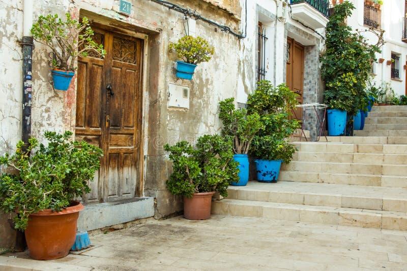 Casas residenciais velhas no estilo medieval com portas de madeira, terracota e os vasos de flores azuis, escadaria, Alicante San imagens de stock