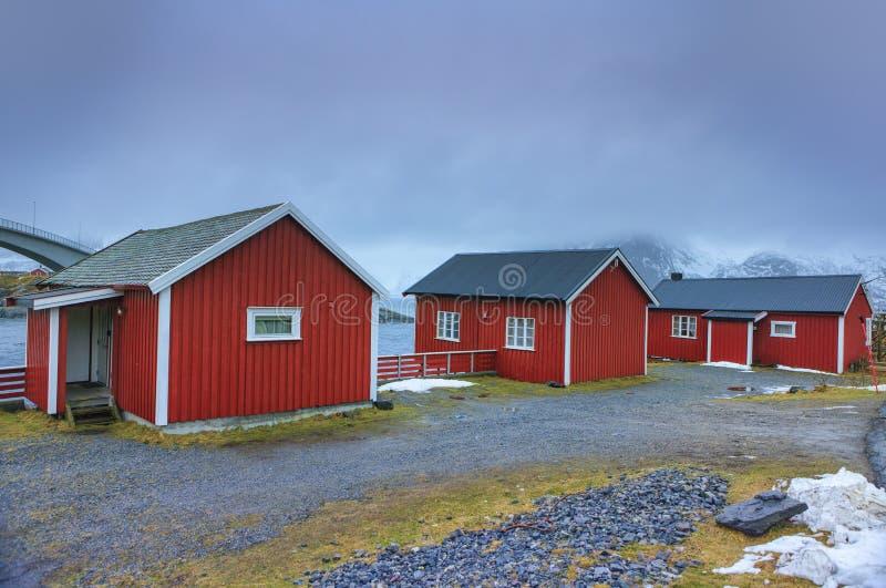 Casas rojas clásicas en una de las calles del pueblo noruego tradicional Hamnoy de la choza de la pesca imagen de archivo libre de regalías