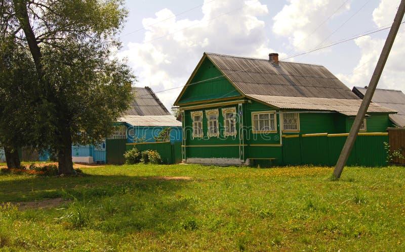 Casas rurais de madeira velhas da vila com o telhado de inclinação ao lado da clareira gramínea verde, das árvores e da estrada R imagem de stock