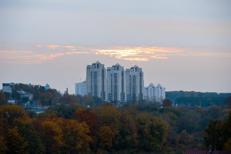 Casas sob o por do sol, nuvens alaranjadas sobre construções do multi-andar imagem de stock