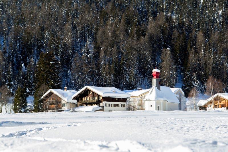 Casas suizas del pueblo de las montañas y una pequeña iglesia con una bóveda roja i foto de archivo libre de regalías