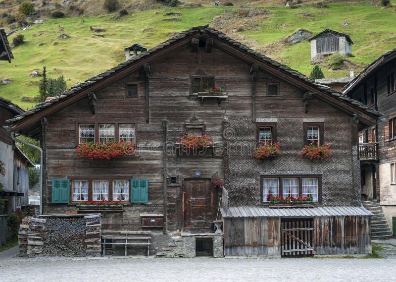 Casas suizas tradicionales de las montañas en el pueblo Suiza alpina de los vals foto de archivo