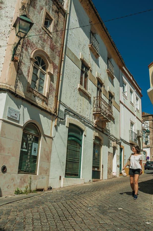 Casas velhas e mulher que andam abaixo da rua imagem de stock