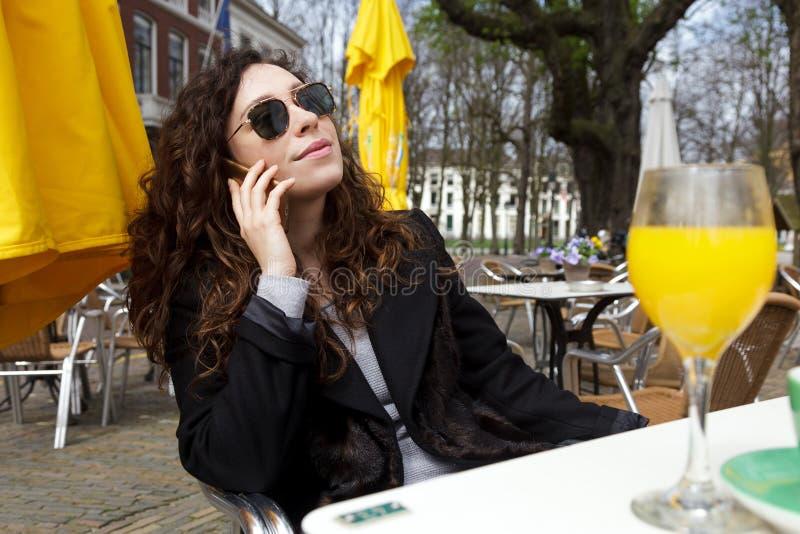 Casas velhas Netherland Haia fl da rua móvel do sorriso de uma comunicação de Europa do telefone celular do cabelo encaracolado d foto de stock royalty free
