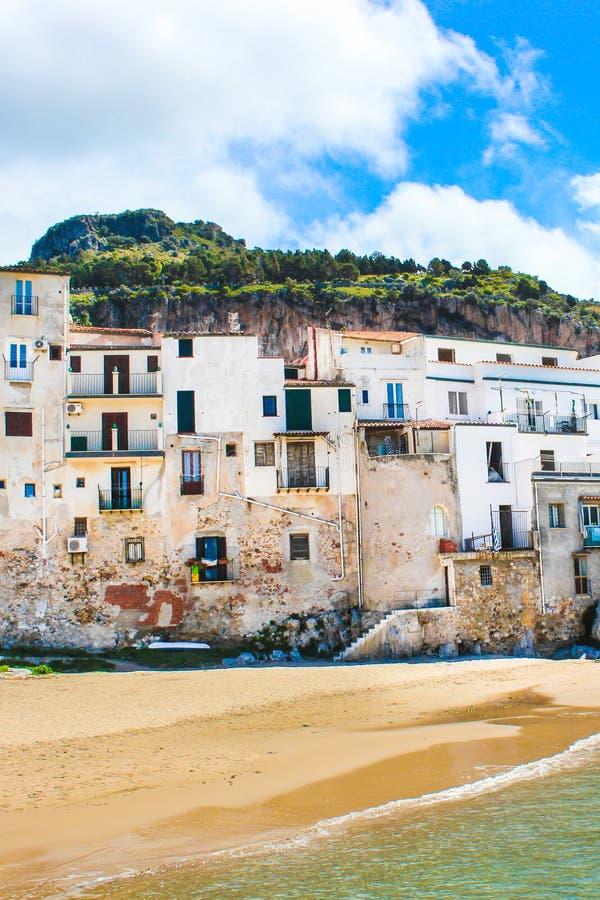 Casas viejas hermosas que pasan por alto el mar tirreno en Cefalu, Sicilia, Italia Capturado en imagen vertical con una roca detr foto de archivo