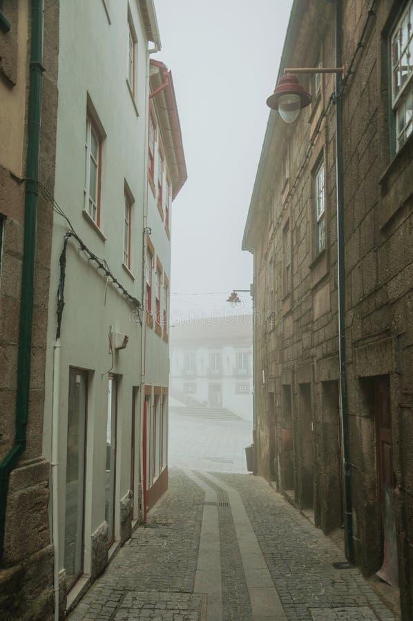 Casas viejas y callejón abandonado en la niebla de la mañana fotos de archivo
