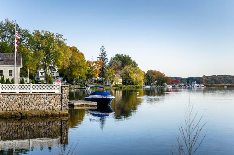 Casas y barcos de la orilla del agua amarrados a los embarcaderos de madera debajo de un cielo claro otoñal imagen de archivo