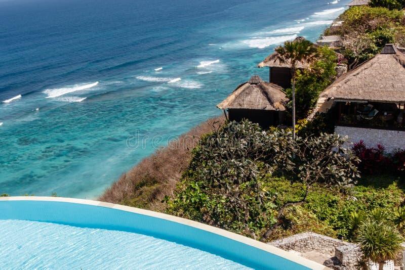 Casas y piscina del infinito en el acantilado sobre Karma Beach en Ungasan, Bali, Indonesia foto de archivo libre de regalías